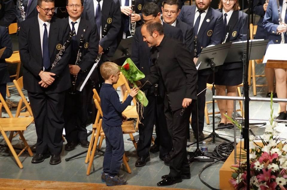 Un xiquet lliura un ramell de flors al director de la banda de Xixona El Trabajo./FOTO BANDA EL TRABAJO
