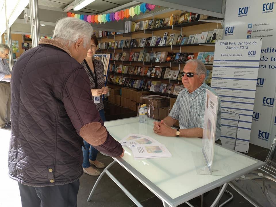 Un visitante de la Feria del Libro de Alicante se interesa por la obra de Vicente Pla.