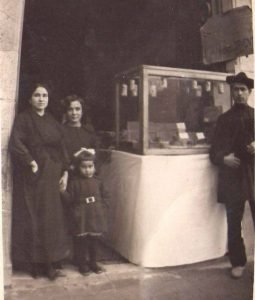 La primera generación de turroneros artesanos Made in Jijona, el hombre con el típico sobrero de roeta y blusón xixonenc, la esposa e hijas, en su portal tienda de la calle Monturiol de Figueres./FOTO JUAN VERDÚ SIRVENT