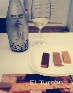 Una botella de Marina Espumante de Bocopa con tres porciones del turrón catado: yema tostada, Jijona y a la piedra./FOTO ESCUELA CATAS ALICANTE