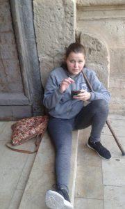 Noelia, una jove pelegrina xixonenca que s'estrenava este any, sentada en la porta de la basílica./FOTO TONI MARINA
