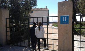 Visitantes senderistas del Pou de la Neu contemplan el edificio del hotel desde la puerta metálica exterior./FOTO MADE IN JIJONA