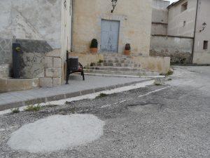 Clot a l'asfalt tapat amb cement pels propis veïns junt a altre sense tapar en la plaça de La Sarga, amb l'esglèsia al fons./FOTO MADE IN JIJONA