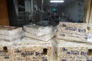Barras de turrón tipo Alicante, el de textura dura, de Hijos de Manuel Picó, con vista parcial de la fábrica y el obrador al fondo./FOTO MADE IN JIJONA