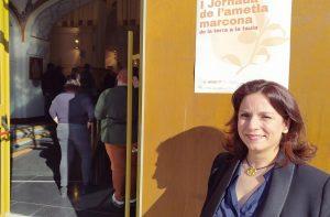 Montse García Gassió delante de un cartel de la jornada de la almendra marcona en la puerta del Teatret de Xixona./FOTO MADE IN JIJONA